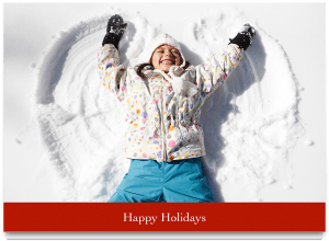gilr making snow angel with happy holidays words